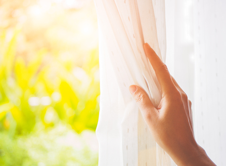 Photo pour Woman's hand opening curtains in the bedroom with natural light and garden background. - image libre de droit