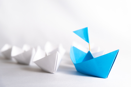 Foto de Leadership concept. blue paper ship with flag lead among white. One leader ship leads other ships. - Imagen libre de derechos