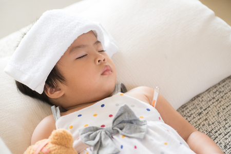 Young little girl sleeping and sick on the sofa with cooler gel on her head and measuring temperature by thermometer. and take care by her mom.