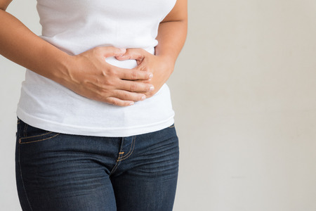 Young woman having painful stomachache. Chronic gastritis. Abdomen bloating concept.