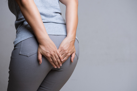 Photo pour Woman suffering from hemorrhoids and hand holding her bottom because having Abdominal pain. Health care concept. - image libre de droit
