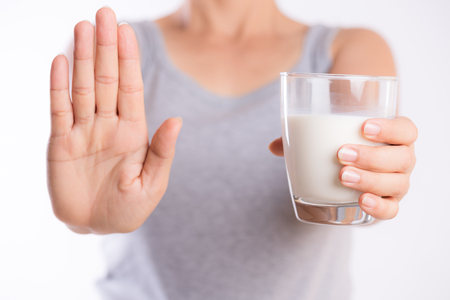Photo pour Woman hand holding glass of milk having bad stomach ache because of Lactose intolerance and another hand shows stop sign. health problem with dairy food products, Healthcare and medical concept. - image libre de droit