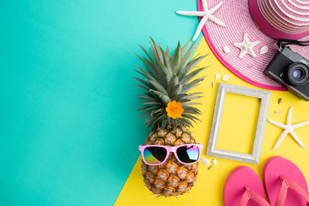 Beach accessories retro film camera, pineapple, sunglasses, flip flop starfish beach hat and sea shell on pink and yellow background for summer holiday and vacation concept.