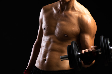 Foto de Closeup of a strength fitness body with dumbbell. Fit young man with beautiful torso. Bodybuilder and muscular body concept. - Imagen libre de derechos
