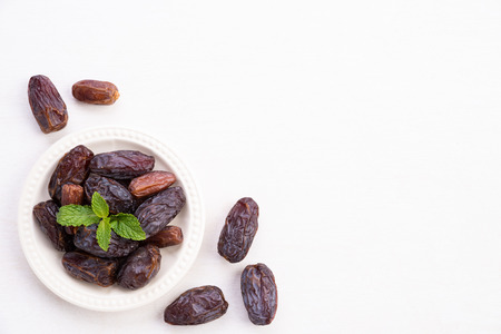 Foto de Ramadan food and drinks concept. Dates fruit and green Mint leaves in a bowl on a white wooden table background. Top view, Flat lay. - Imagen libre de derechos