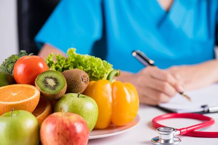 Photo pour Healthy lifestyle, food and nutrition concept. Close up of fresh vegetables and fruits with stethoscope lying on doctor's desk. - image libre de droit
