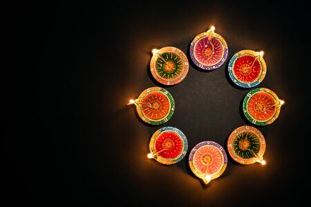 Photo pour Happy Diwali - Clay Diya lamps lit during Dipavali, Hindu festival of lights celebration. Colorful traditional oil lamp diya on white background - image libre de droit