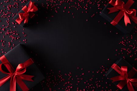 Photo for Top view of black christmas boxes with red ribbon on black background with copy space for text. black Friday composition. - Royalty Free Image