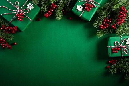 Photo pour Christmas background concept. Top view of Christmas green gift box with decoration, spruce branches and red berries on green  background. - image libre de droit