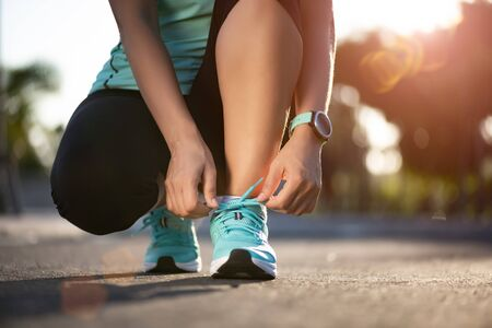 Photo pour Running shoes - closeup of woman tying shoe laces. Female sport fitness runner getting ready for jogging in garden background. - image libre de droit