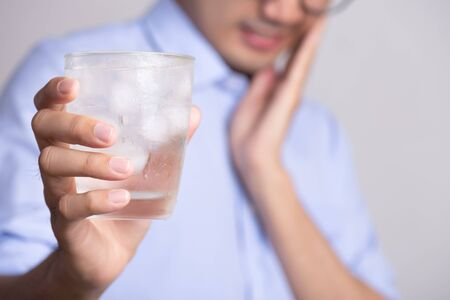 Photo pour Young man with sensitive teeth and hand holding glass of cold water with ice. Healthcare concept. - image libre de droit