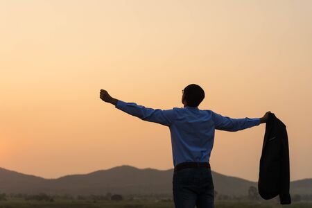 Photo for A happy asian handsome young businessman spreading arms and holding his business suit during sunset sunrise mountain in background. Business success concept. - Royalty Free Image