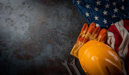 Photo pour Happy Labor day concept. American flag with different construction tools on dark stone background, with copy space for text. - image libre de droit