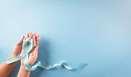 Photo pour World diabetes day awareness concept. Hand holding blue ribbon, symbolic bow color raising awareness in diabetes day on pastel background,  14 November. - image libre de droit