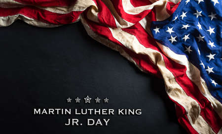 Foto de Martin Luther King Day anniversary concept. American flag against black wooden background - Imagen libre de derechos