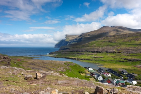 Small settlement on the sea in the midst of green mountains . Faroe Islands landscape .