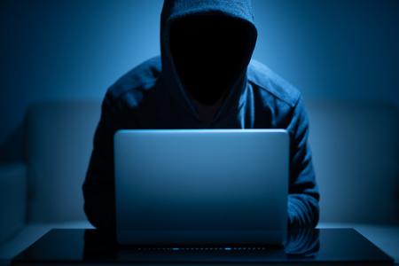 Photo pour Hacker dark face using laptop in the dark room - image libre de droit