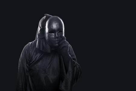 Foto de Scary figure in hooded cloak with mask in hand isolated on black background - Imagen libre de derechos