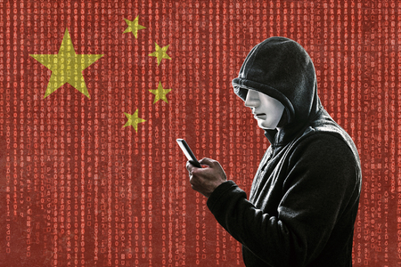 Photo pour Chinese hooded hacker with mask holding smartphone - image libre de droit