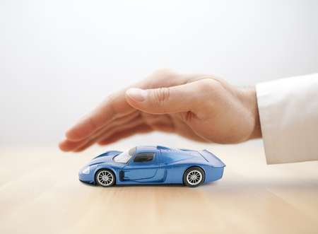 Photo for Car insurance concept with blue car toy covered by hand - Royalty Free Image