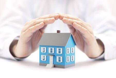 Photo pour Small blue house covered by hands - image libre de droit