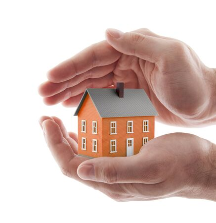 Photo pour Small orange toy house protected by hands isolated on white - image libre de droit