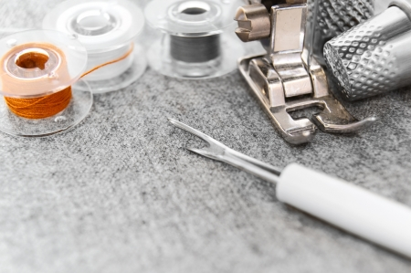 The sewing machine, threads and thimbles on a fabric