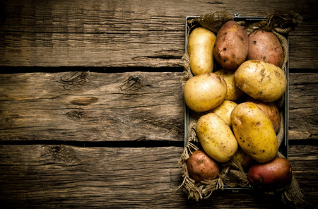 Potatoes in an old box on a wooden table