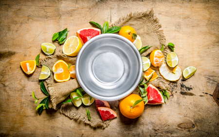 Empty the bowl of fruit around citrus - grapefruit, orange, tangerine, lemon, lime the old fabric. On wooden background. Top view