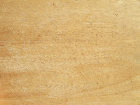 Old and used natural wooden cooking board with cuts