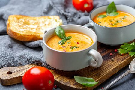 Photo pour Delicious tomato soup with spices and green basil in ceramic pot on wooden serving board, selective focus. - image libre de droit