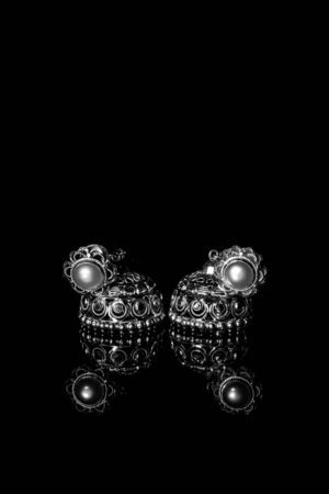 Photo pour Earring Gold Jewelry Traditional With Stones and Two Golden earrings with reflection . Pair of golden earring with pearl tone on black background. Luxury female jewelry, close-up - image libre de droit