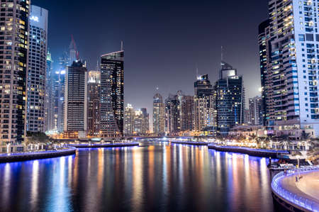 Photo pour 28th JAN, 2021 DUBAI. Dubai Marina skyline with illuminated sky scrappers,buildings and moving boats showing reflection on water captured from Marina Mall , Dubai, UAE. - image libre de droit
