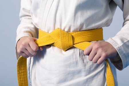 Photo pour Hands tightening yellow belt on a teenage dressed in kimono for martial arts - image libre de droit