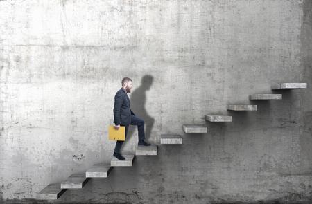 Foto de Side view of a man climbing up the steps in a blank concrete wall. 3d render - Imagen libre de derechos