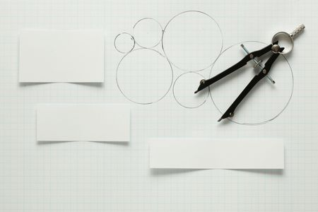 Blank pieces of paper with pen & compass