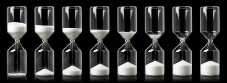 Foto de Collection of hourglasses with white sand showing the passage of time - Imagen libre de derechos