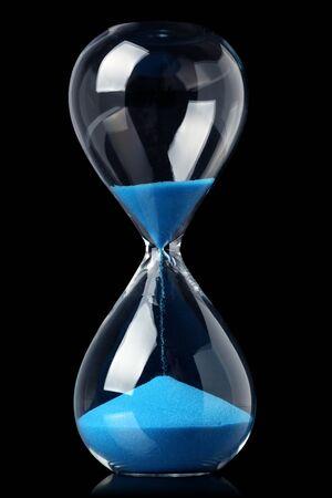 Photo pour Hourglass with blue sand showing the passage of time - image libre de droit