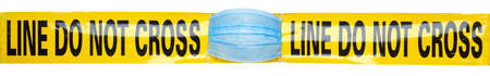 Photo for Yellow DO NOT CROSS police tape with medical face mask. Quarantine concept. - Royalty Free Image