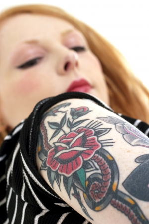 Strawberry Blonde Red Head looking down at her forearm with shallow depth of field covered in tattoos.