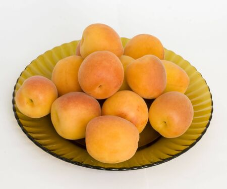 ripe apricots on a dish from brown glass