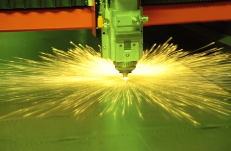 Laser cutting metal sheet in factory, with sparks flying around