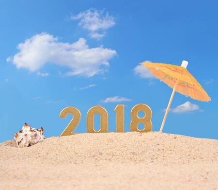 Photo pour 2018 year golden figures with seashell on a beach sand - image libre de droit