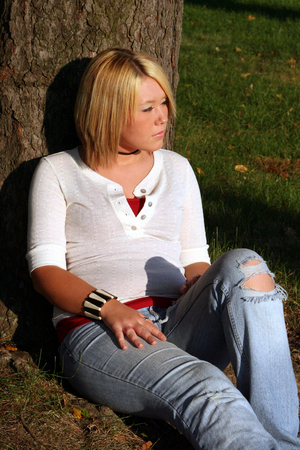 Serious young woman sitting on the ground leaning against a tree with the sun shining directly on her.