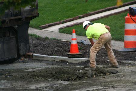 Road worker shoveling broken asphalt at a work site.