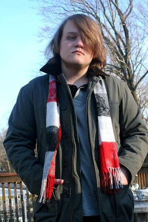 Teenage boy with a serious expression, taken outdoors in winter.