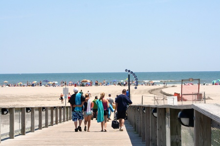 Group of young adults walking down a boardwalk ramp toward the beach in Wildwood, New Jersey.
