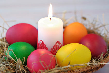 Photo for In the wicker basket lie Easter eggs and a burning candle. Close-up view. - Royalty Free Image