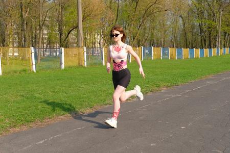 Foto de Girl with kinesio tape on her body running on lost stadium track in spring park. - Imagen libre de derechos