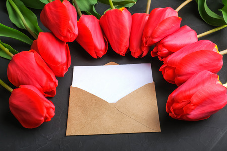 Foto de Mockup of fresh red tulips bouquet and blank greeting card in kraft envelope on dark background with copy space. Close up view - Imagen libre de derechos
